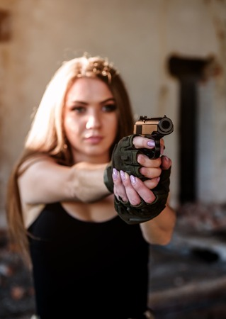 cute girl in military glowes with gun