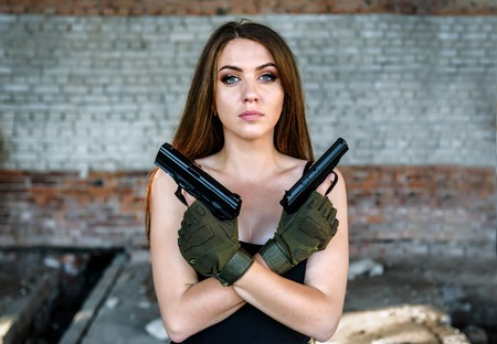 portrait of beautiful military girl with two guns