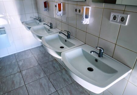 four clean washbasins with faucet in the toilet Stock Photo
