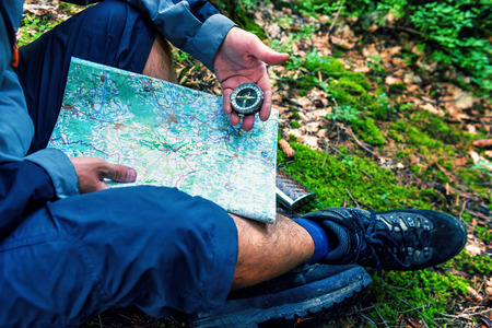 tourist man in forest with compass and map
