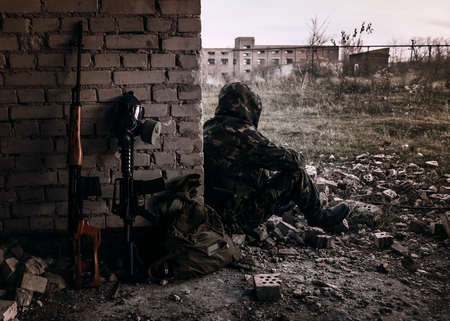Sniper rifle, gas mask and soldier. Photo tonned in dark tones. Stalker theme. Nuclear post-apocalypse survivors