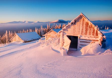 Abandoned cabins in snowdrift. Beaautiful landscape in winter Carpathian mountains on amazing sunrise