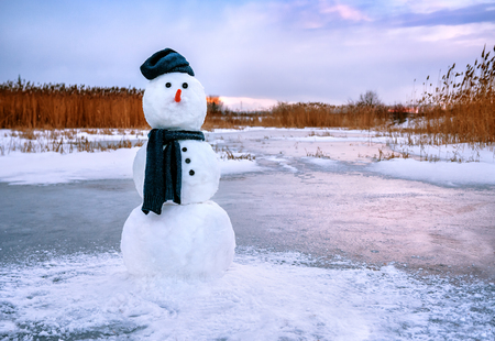 cute snowman in grey scarf on sunset