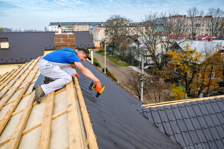 a professional master (roofer) with electric screwdriver covers repairs the roof Фото со стока