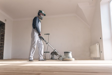 Man (master ) clean the parquet with special polishing machine