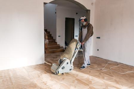a professional master grinding (cleaning) a parquet floor Standard-Bild - 118884411