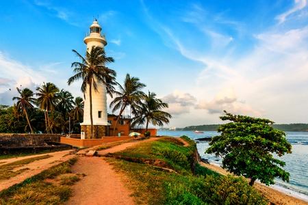 white lighthouse in fort Galle Sri Lanka on sunset Фото со стока