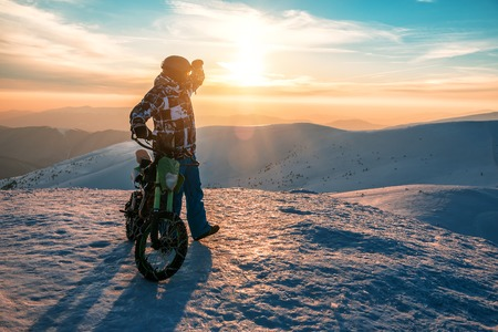 man with motorbike in winter mountains on sunset