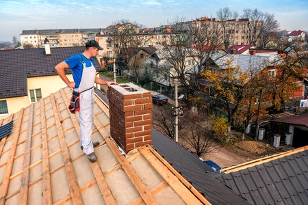 a professional master (roofer) with electric screwdriver covers repairs the roof near the chimney