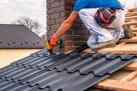 ein professioneller Meister (Dachdecker) mit Elektroschrauberabdeckungen repariert das Dach in der Nähe des Schornsteins