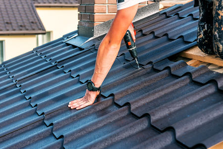 a professional master (roofer) with electric screwdriver covers repairs the roof Stock Photo