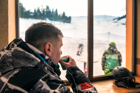skier resting with with cup of coffee on ski resort Stock Photo