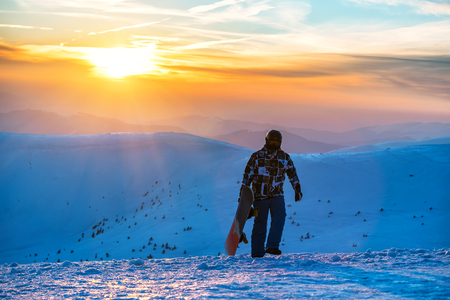 snowboarder with snowboard on beautiful sunset in the hight mountains