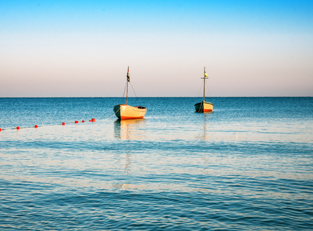 two boats in a calm sea on sunrise Stock Photo