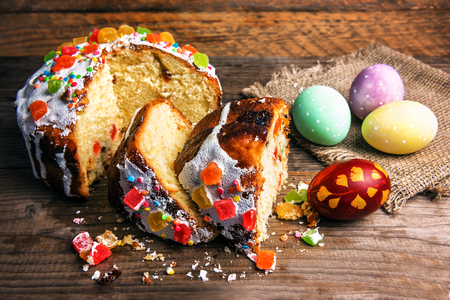 chopped easter cake with painted eggs on wooden background