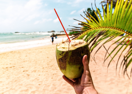 delicious fresh juicy coconut in hand on the tropical beach Stock Photo