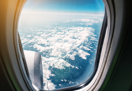Snow-capped mountains through the window of the plane. Travel time