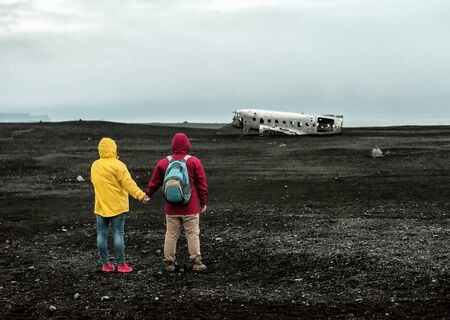 a tourist couple are looking at the wreck of the broken plane in Iceland Banque d'images - 126378415