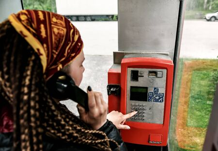 a girl with dreadlocks speaks by vintage payphone Banque d'images - 126378416