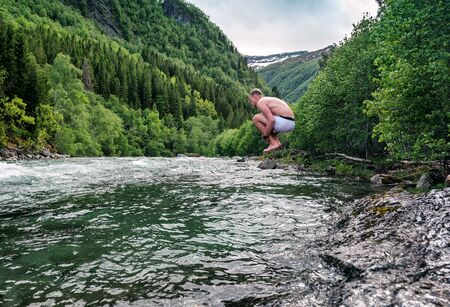 young man jump into a cold mountain river in Norway Banque d'images - 126378417