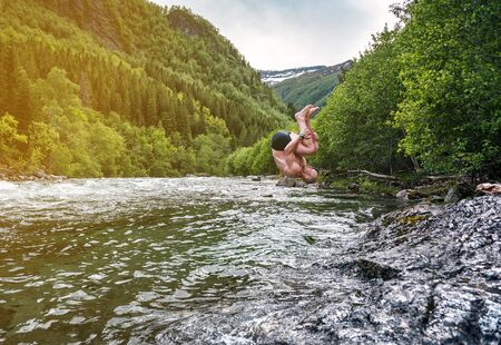 man jumps salto into a mountain river in Norway Banque d'images - 126378418