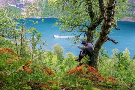 man sits on a tree above a high cliff in Gejrangerfjord in Norway Banque d'images - 126378419