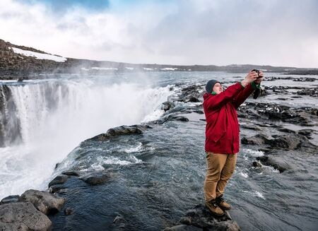 man takes a selfie on the background of a waterfall Dettifoss in Iceland Banque d'images - 126378421