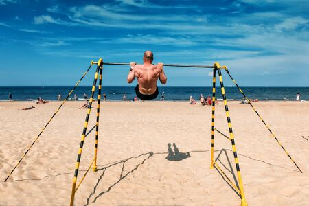a young sports man doing exercises on the beach bar Banque d'images - 126378422