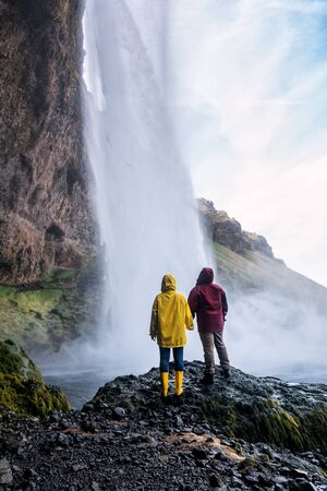 couple in bright clothes looks at an Icelandic waterfall Seljalandsfoss Banque d'images - 126378427