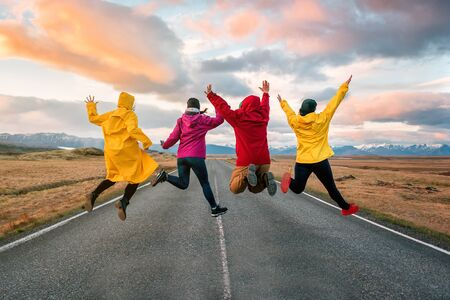 four friend jump on the road at sunset in Iceland Banque d'images - 126381961