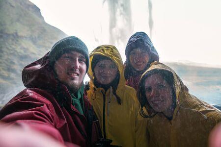 four friends in raincoats make a selfie under an Icelandic waterfall Seljalandsfoss Banque d'images - 126380036