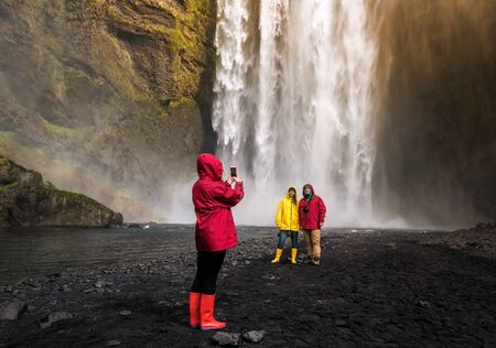 friends are photographed before a waterfall Skogafoss in Iceland Banque d'images - 126380039