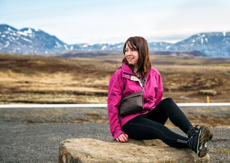 tourist girl in a violet jacket sits on the stone in Iceland Banque d'images - 126380041