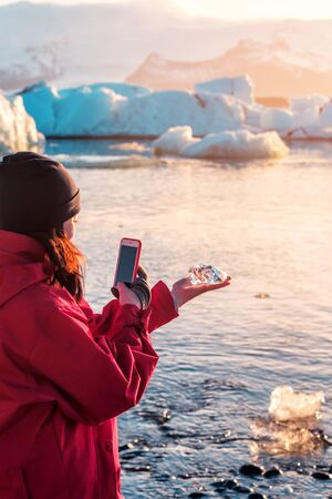 girl photographing a piece of ice in ice lagoon in Iceland Banque d'images - 126380042