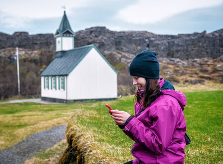 tourist girl with a smartphone sits near a church in Iceland Banque d'images - 126380044