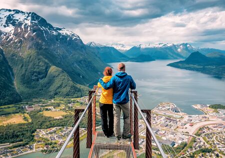 happy blue yellow couple tourists stands on rampestreken in Norway Banque d'images - 126380046