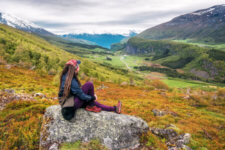 hiking girl with dreadlocks is sitting on the rock in Norway Banque d'images - 126380048