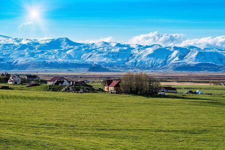 Icelandic farm and huge glacier. Beautiful sunny landscape Banque d'images - 126380054