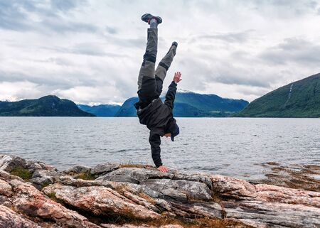 man sdand on one hand on the rock in Iceland Banque d'images - 126379965