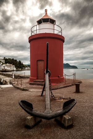 old anchor and lighthouse in Alesund under cloudy sky Banque d'images - 126379973