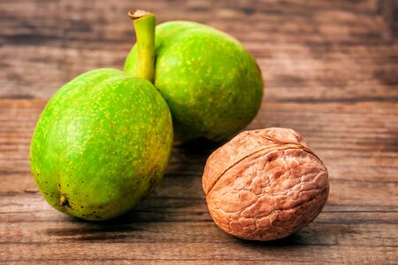 Fresh harvest of walnuts on a wooden background. Green and brown nuts. Shell and peel of walnuts. Banque d'images - 126379983