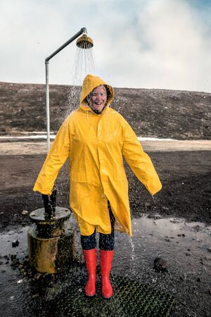 The girl in a yellow raincoat take the shower in open field in Iceland Banque d'images - 126379928