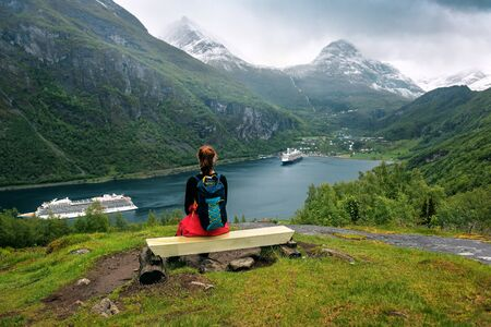 The girl with backpack is sitting on the bench under Gejrangerfjord. Norway Banque d'images - 126378242