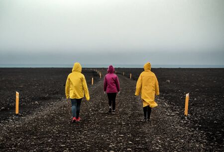 three girls in bright clothes go along the Icelandic road on black sand Banque d'images - 126378246