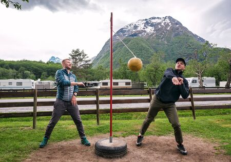 two friends are playing tetherball game in Norwegian camping Banque d'images - 126378252