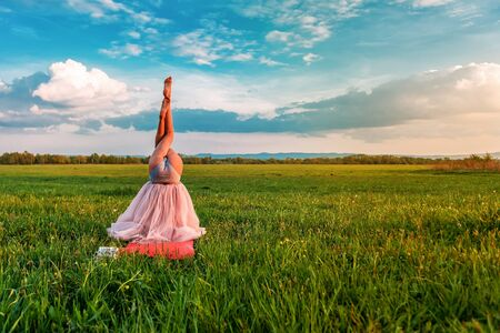 Yoga girl in the field stands on the head with pink dress on the head on sunset. Funny photo Banque d'images - 126379934