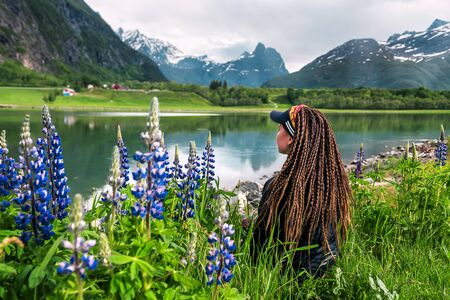 young girl with dreadlocks is sitting in Lupin on riverbank in Norway Banque d'images - 126379940