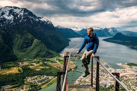 young man is sitting on rampestreken in Norway. Andalsnes Banque d'images - 126379941