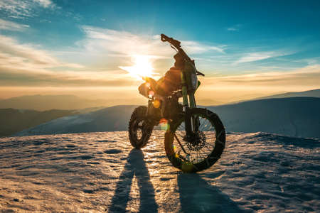 a motorcycle with chains on wheels stands on top of a mountain in winter at sunset 스톡 콘텐츠