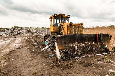 yellow bulldozer on garbage dump (landfill)